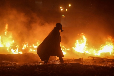 A pro-European integration protester walks among burning tyres at the site of clashes with riot police in Kiev