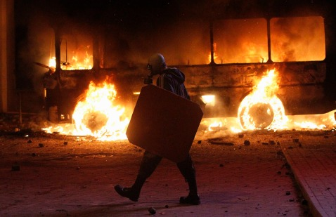 A pro-European integration protester walks past a burning police bus during a rally near government administration buildings in Kiev