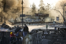 Police troops stand in front of a barricade at the site of clashes with anti-government protesters in Kiev