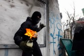 A pro-European integration protester carries a Molotov cocktail during clashes with police in Kiev